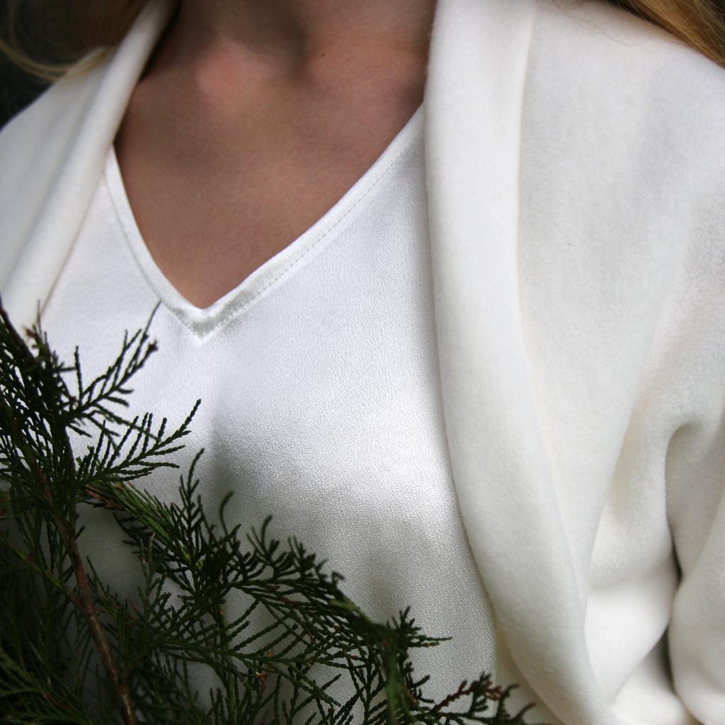 Die schlichte Schnittführung der Hochzeitsjacke macht dieses Modell zu einem beliebten Klassiker bei den Winterhochzeiten. Brautmode ma-eins aus münchen