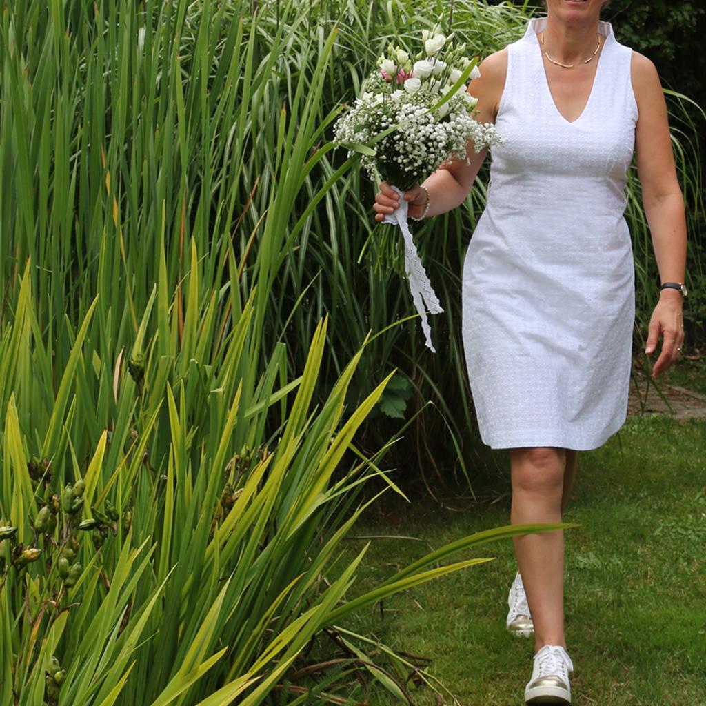 das weiße Hochzeitskleid ist Knie umspielend und leicht ausgestellt.  Ärmellos und luftig. ein ideales Kleid für das Standesamt.