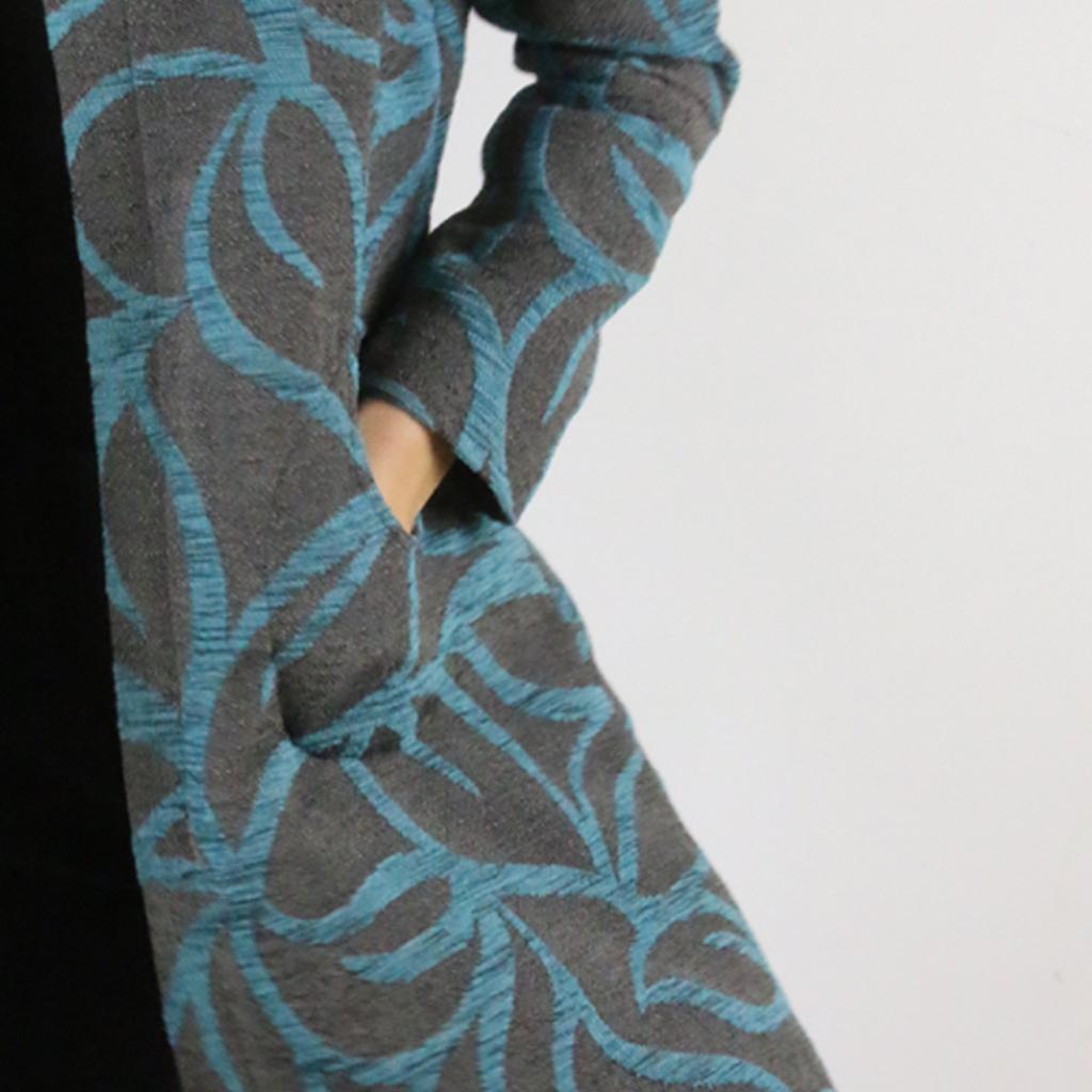 Der Designmantel von ma-eins hat die klassischen Kreisrunden Taschen. Designmode aus München.