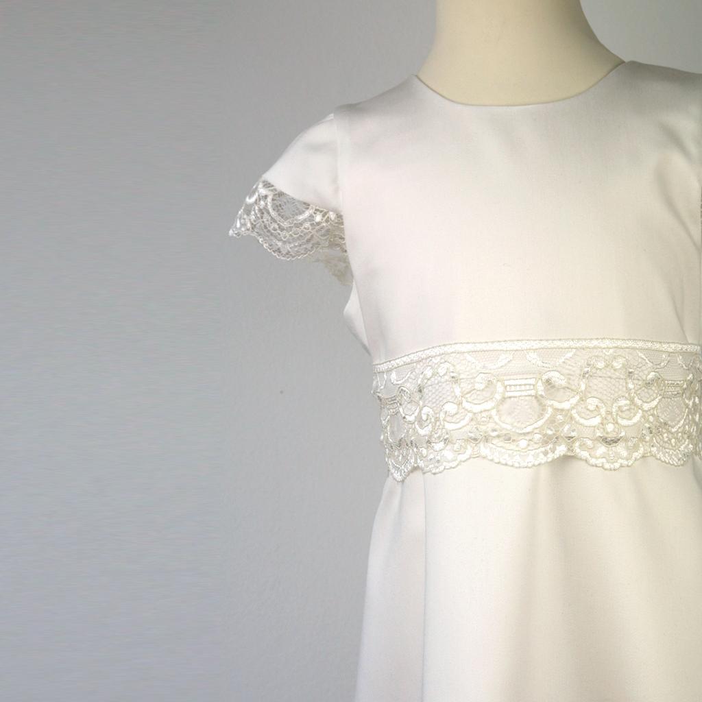 Das schlichte Kleid ist mit Spitze eine schönes Kommunionkleid mit breitem Spitzengürtel.